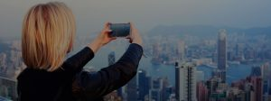 Blonde girl uses the latest mobile technology to take a picture of the city | Fon