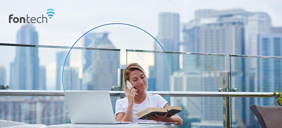 Woman talking on phone using laptop enjoying seamless connectivity thanks to Fontech's technology